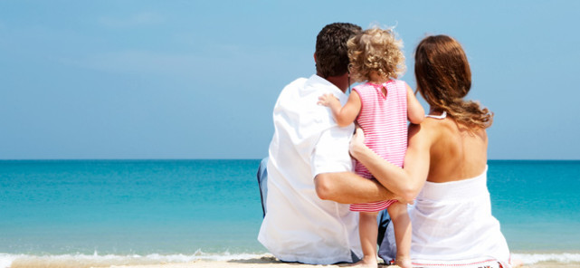 Parents and a young child sitting on a beach